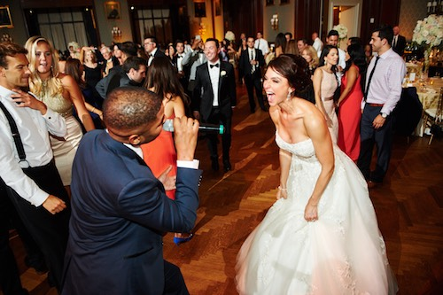 A beautiful bride sings along with the All About Me Band on the dance floor at her wedding.