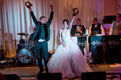 This bride and groom are on the stage rocking their tambourines in the air with the Contagious Band of BVTLive.